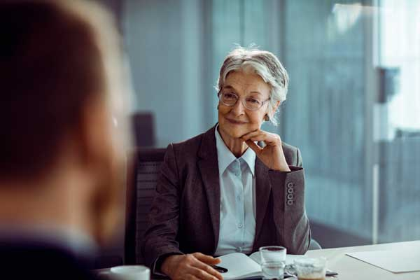 A female executive with glasses considers a staffing option from Scion Staffing that she's interviewing